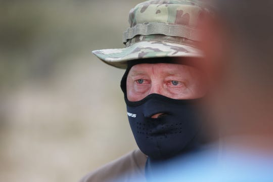 """Viper"", a member of the United Constitutional Patriots - New Mexico Border Ops begins to tear up after he is evicted from their camp Tuesday, April 23, in Anapra, N.M. Union Pacific police told them they would no longer be able to camp at their current site on Union Pacific property."