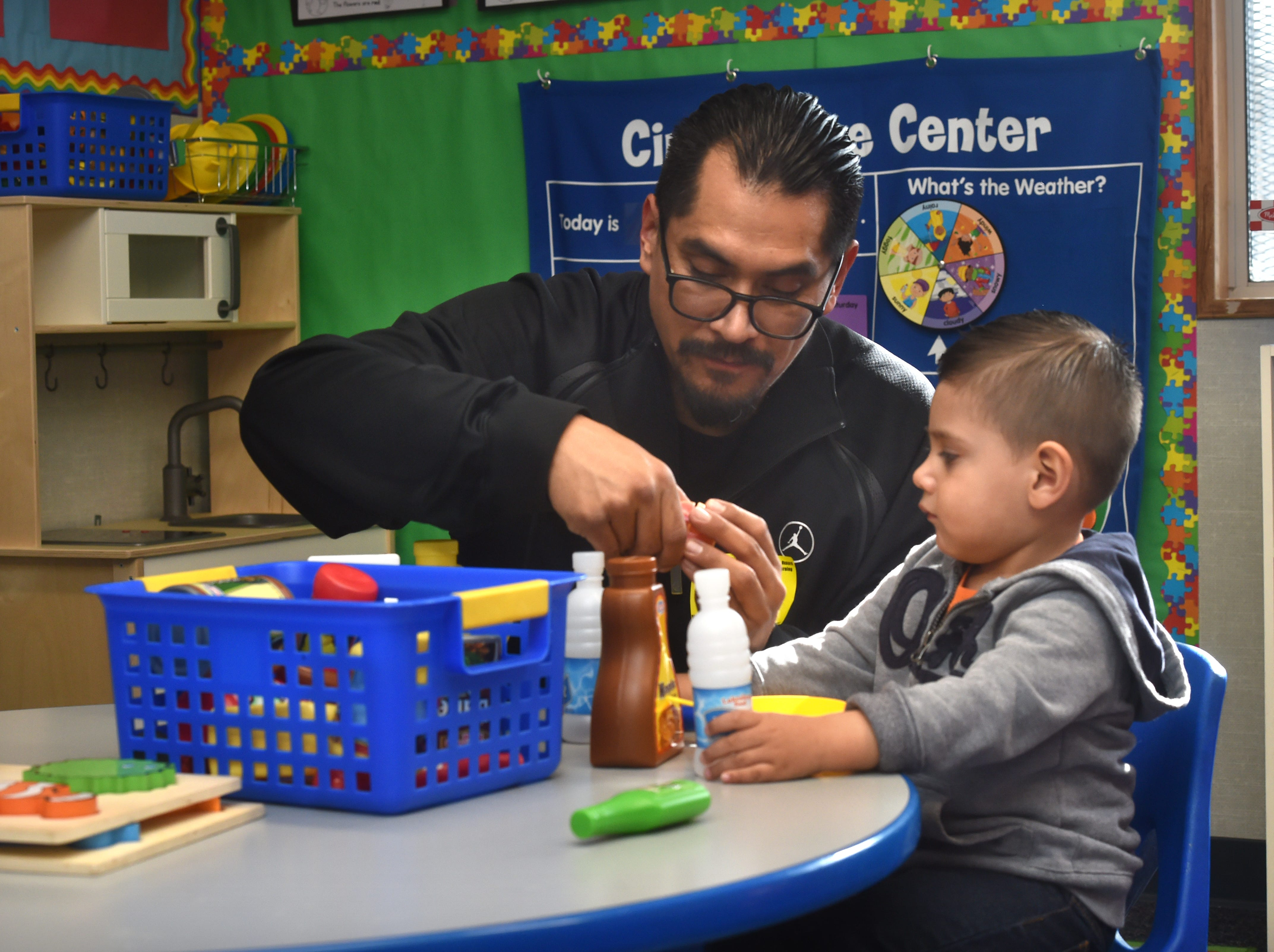 Nelson Tapia and his 18-month-old son Niko play with kitchen items during a First 5 Neighborhoods for Learning class at Hathaway Elementary School in Oxnard on April 23.