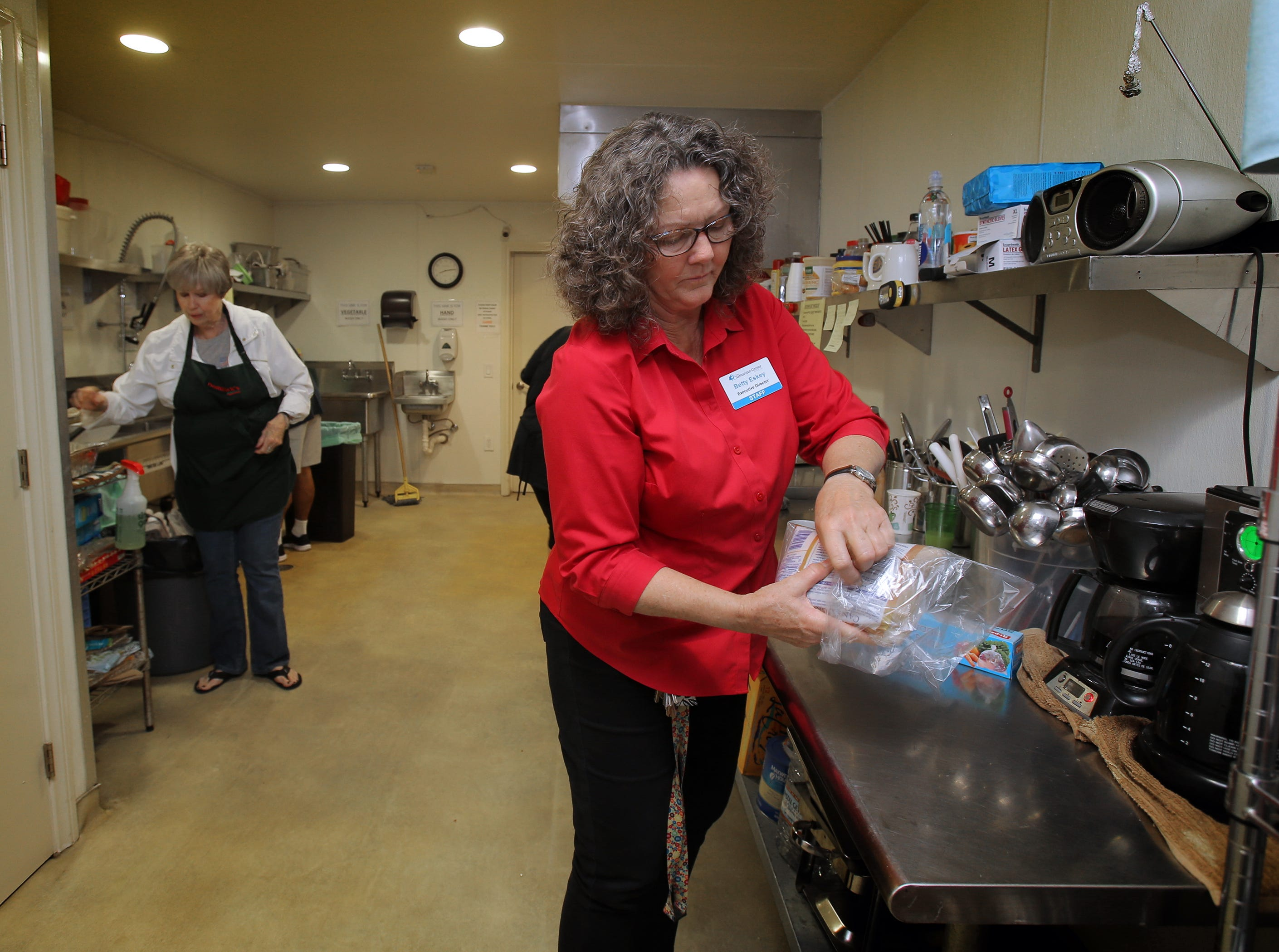 Samaritan Center Executive Director Betty Eskey (foreground) helps out volunteer April Budak in the nonprofit Simi Valley homeless shelter's kitchen as they get ready to serve breakfast.