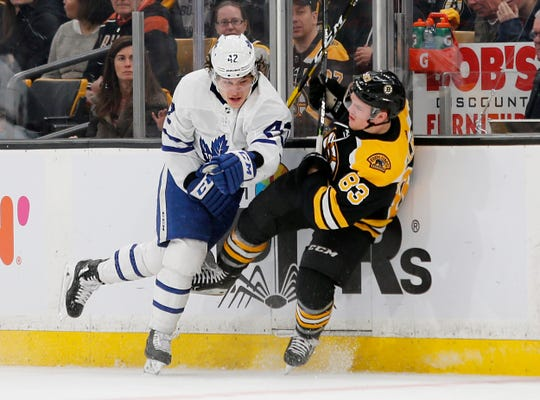 Trevor Moore, left, knocks down the Bruins' Karson Kuhlman during the Maple Leafs' first-round playoff series in 2019. Moore, a native of Thousand Oaks, was traded by Toronto to Los Angeles last week.