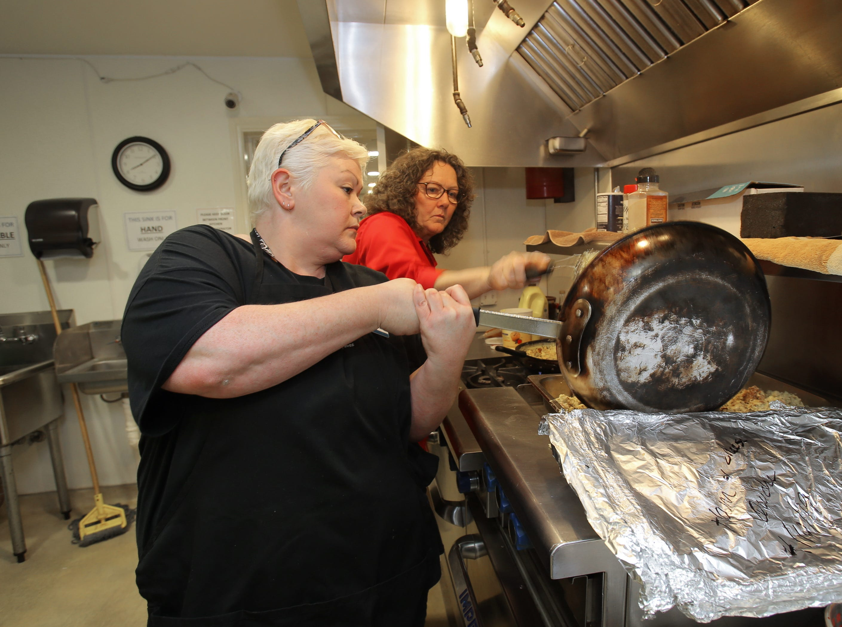 Samaritan Center Executive Director Betty Eskey, right, helps out staff volunteer coordinator Jenna Hayden in the kitchen area as they get ready to serve breakfast at the Simi Valley homeless shelter. After 13 years at the center, Eskey will be retiring in July.