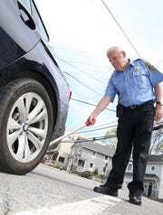 Irvington Parking Enforcement Officer Jimmy Brennan chalks a tire of a car parked on Main Street in Irvington April 23, 2019.