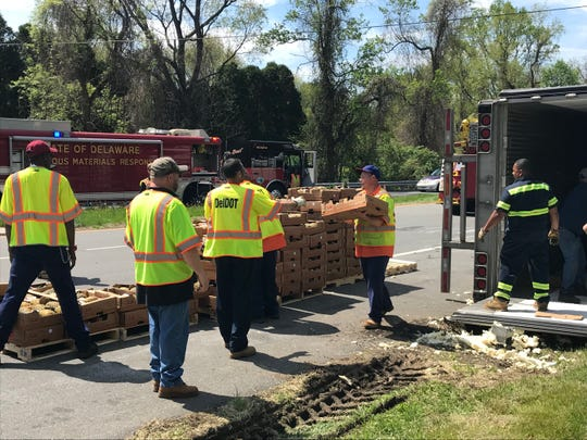 Delaware Department of Transportation workers unload a truck after it overturned off Lancaster Pike, near Hockessin, on Tuesday, April 23, 2019.