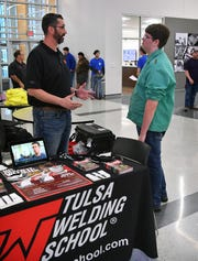 Robert Trout of Tulsa Welding School answers questions for Career Education Center welding student Cooper Wedel, right, during the College and Career Fair Tuesday.
