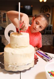 Sophia Shima works on her cake for the Carr Center Cake Auction at her home. The Duncan Falls Elementary School third-grade student is giving back to a place that helped her when she was younger.