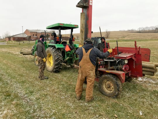 The New Lex FFA moves fence posts to start installing a new fenced area at the farm. The FFA will run the farm to gain real-life experience.
