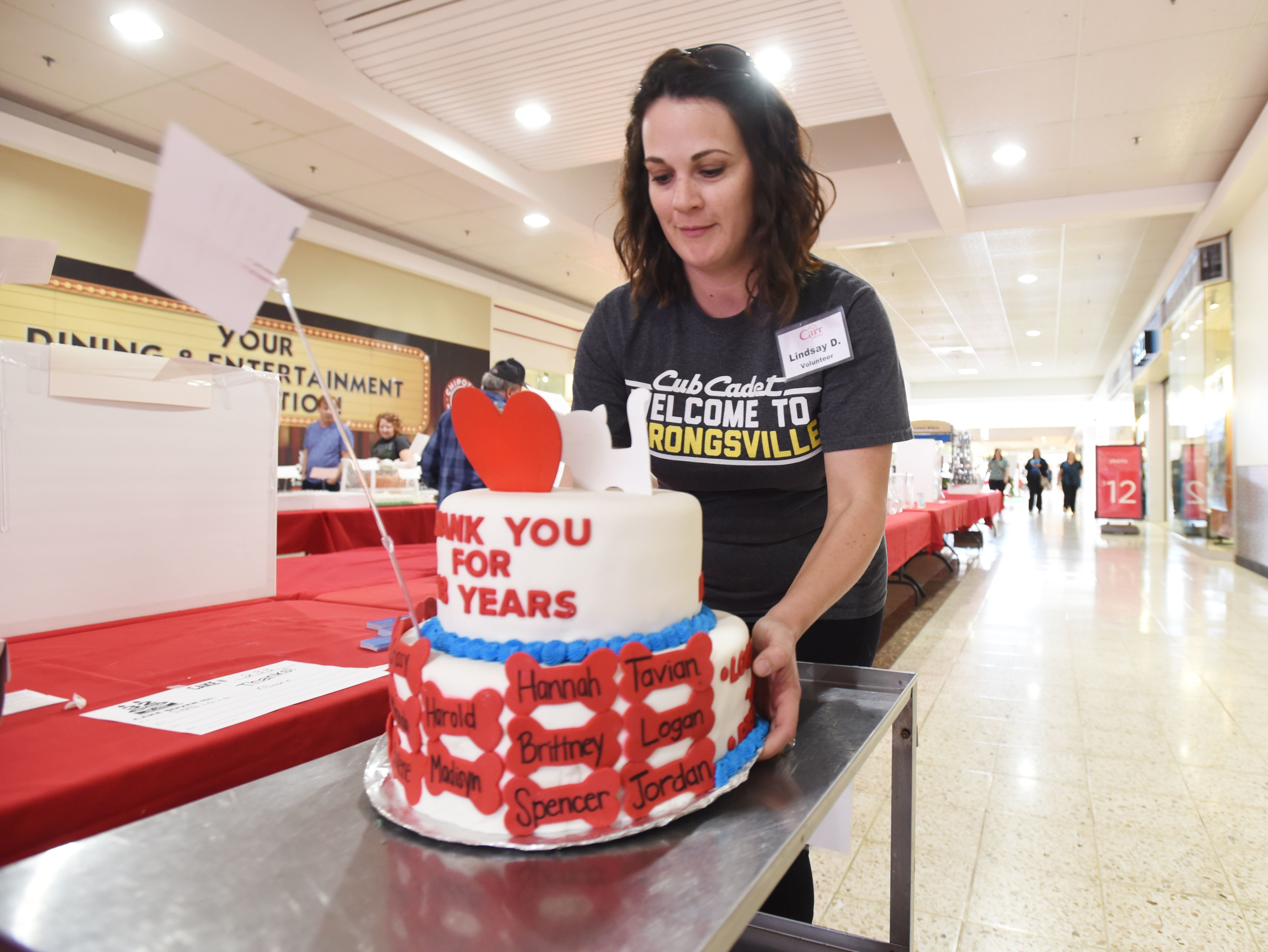 Volunteer Lindsay Dodson of American Pride collects a cake during the Carr Center Cake Auction at the Colony Square Mall.