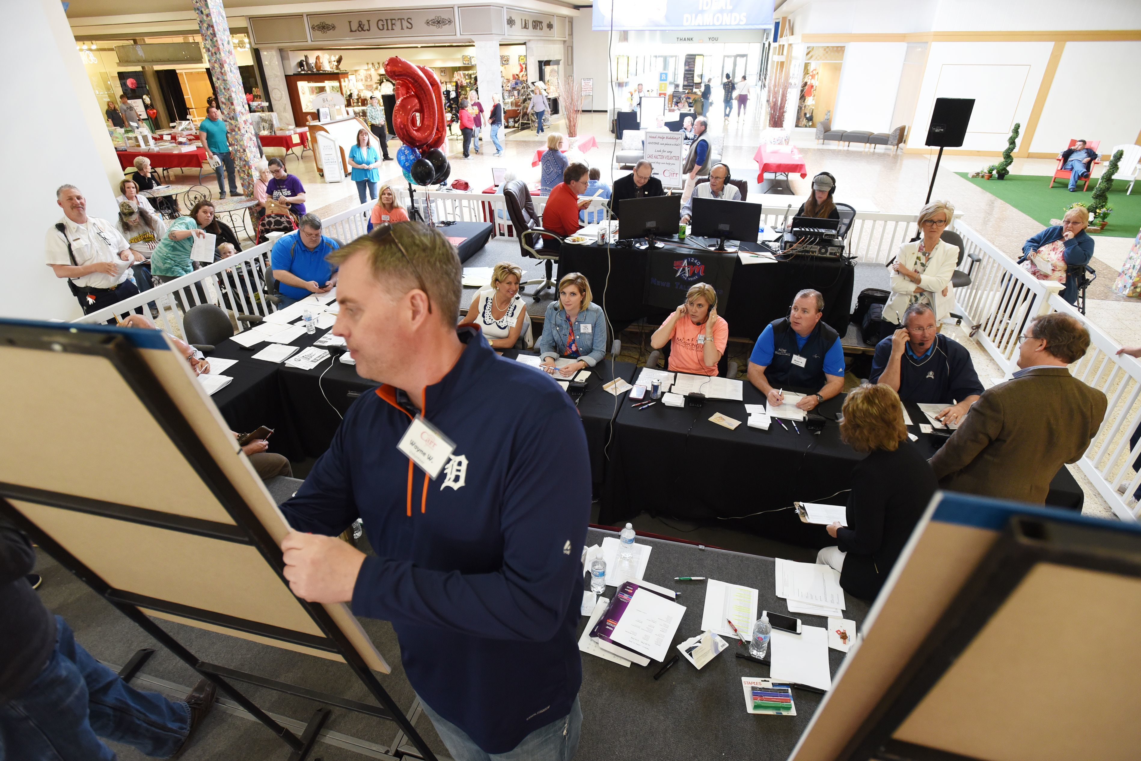 Volunteer Wayne Wycroff of Stratos Wealth Management writes down a bid during the Carr Center Cake Auction at the Colony Square Mall.