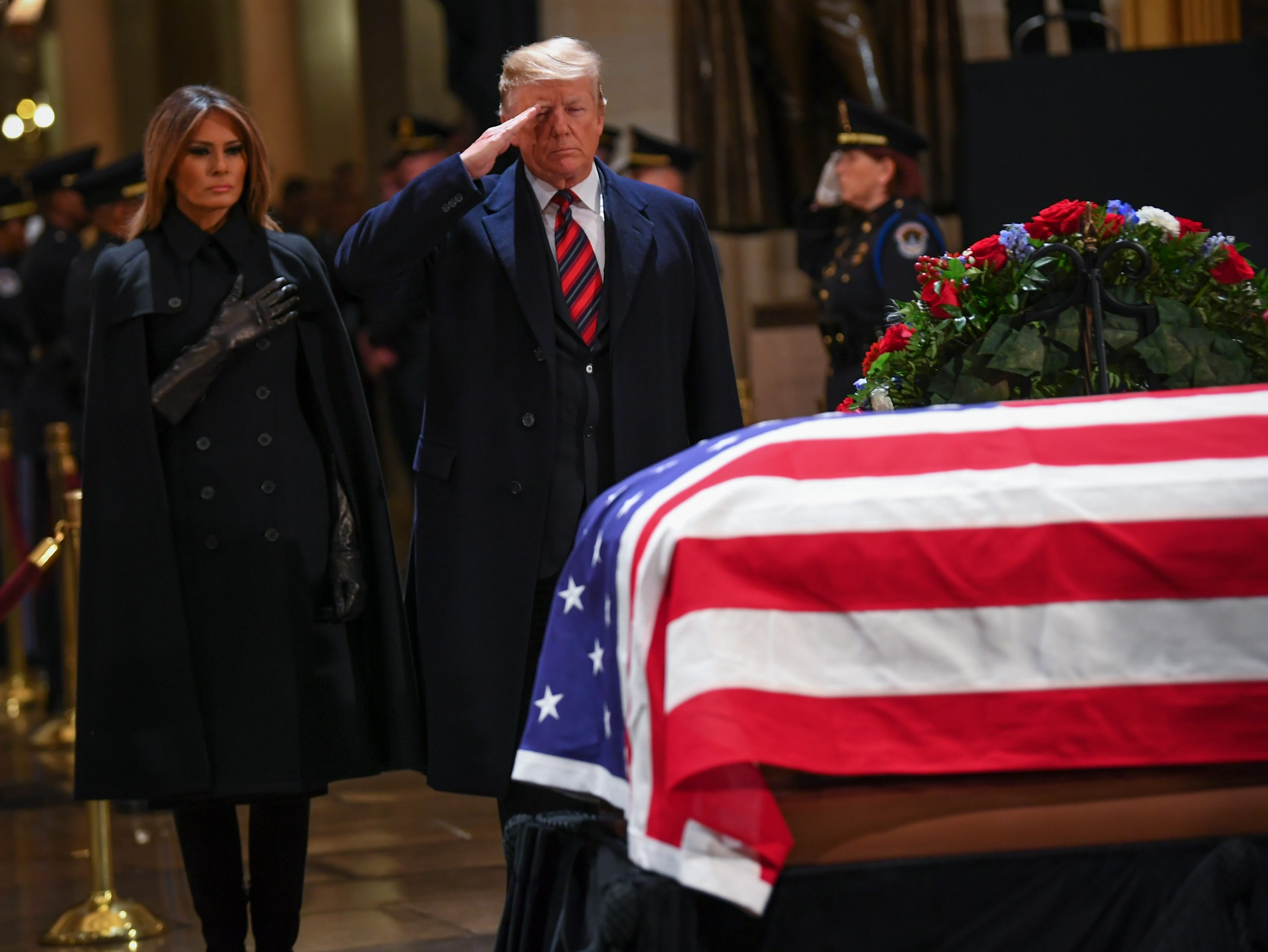 President Donald Trump and First Lady Melania Trump pay their respects to former President George H.W. Bush as the 41st President lies in state at the U.S. Capitol Rotunda on Dec. 3, 2018.