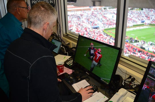 USA TODAY writer George Schroeder looks at a replay during the Georgia spring football game.