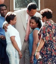 Rev. Jesse Jackson, center, hugs Renee Mullins, in blue, the daughter of James Byrd Jr., while visiting the Byrd family Wednesday, June 10, 1998, in Jasper, Texas. James Byrd Jr. was chained to pickup truck and dragged to his death along a rural East Texas road near Jasper. Three white men have been charged with his murder. Others shown are unidentified. (AP Photo/David J. Phillip) ORG XMIT: XJAS111