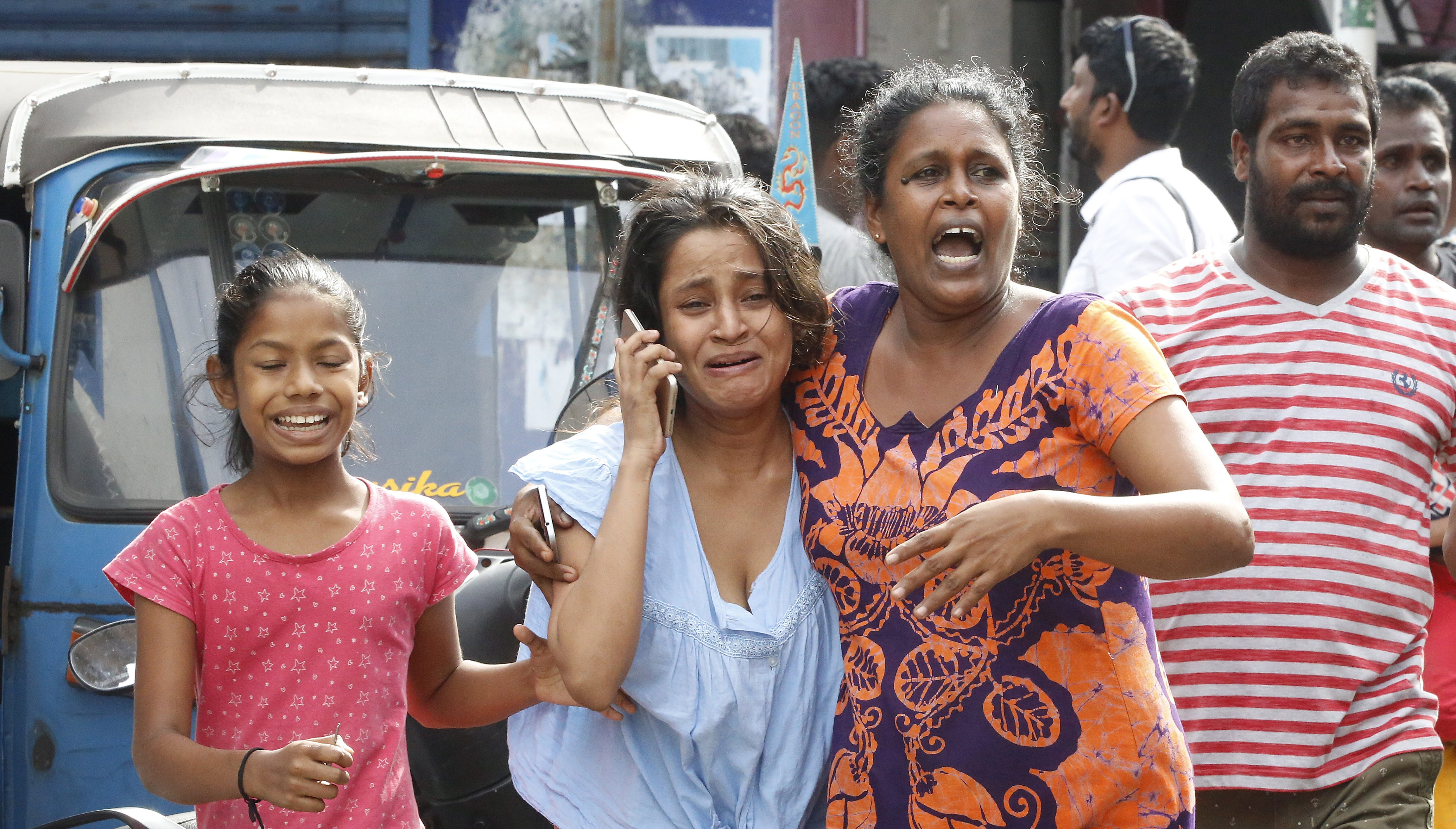 Sri Lankan people run for safety as authorities announced an evacuation of the area after a van was found parked with a suspected explosive device near St Anthony's Church Kochchikade in Colombo, Sri Lanka on April 22, 2019.