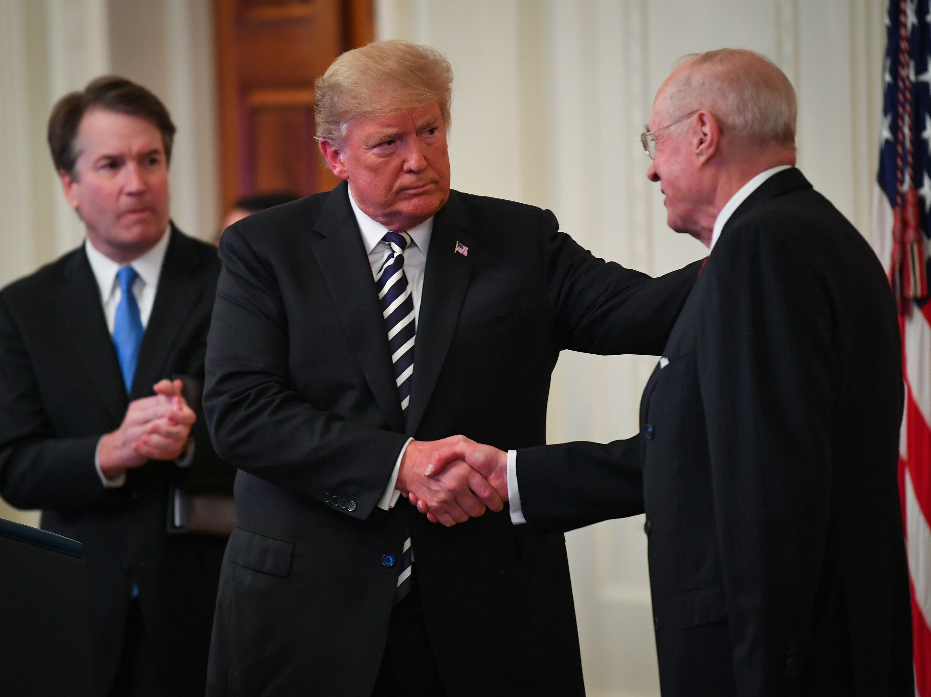 President Donald Trump acknowledges retiring Supreme Court Justice Anthony Kennedy, right, during ceremonial swearing-in held at the East Room of the White House for newly confirmed Supreme Court Justice Brett Kavanaugh, left, on Oct. 8, 2018.