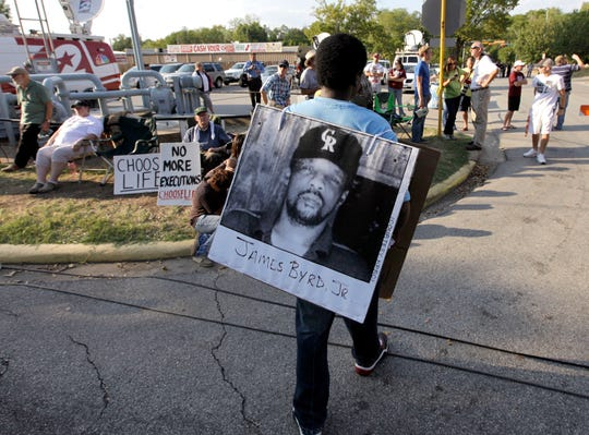 ORG XMIT: TXDP116 Ricky Jason wears a photograph of James Byrd Jr. outside the Texas Department of Criminal Justice Huntsville Unit before the execution of Lawrence Russell Brewer Wednesday, Sept. 21, 2011, in Huntsville, Texas. Brewer, 44, one of two purported white supremacists condemned for the dragging death of James Byrd Jr., was executed Wednesday. Brewer was convicted for his participation in chaining Byrd to the back of a pickup truck, dragging the black man along a rural East Texas road and dumping what was left of his shredded body outside a black church cemetery in 1998. (AP Photo/David J. Phillip)