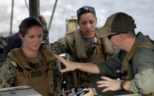 In this Aug. 13, 2013 file photo, U.S. Navy Master-at-Arms Third Class Danielle Hinchliff, left, and Master-at-Arms Third Class Anna Schnatzmeyer, center, participate in a U.S. Navy Riverine Crewman Course under instructor Boatswain's Mate Second Class Christopher Johnson, right, on a Riverine Assault Boat at Camp Lejeune, N.C.