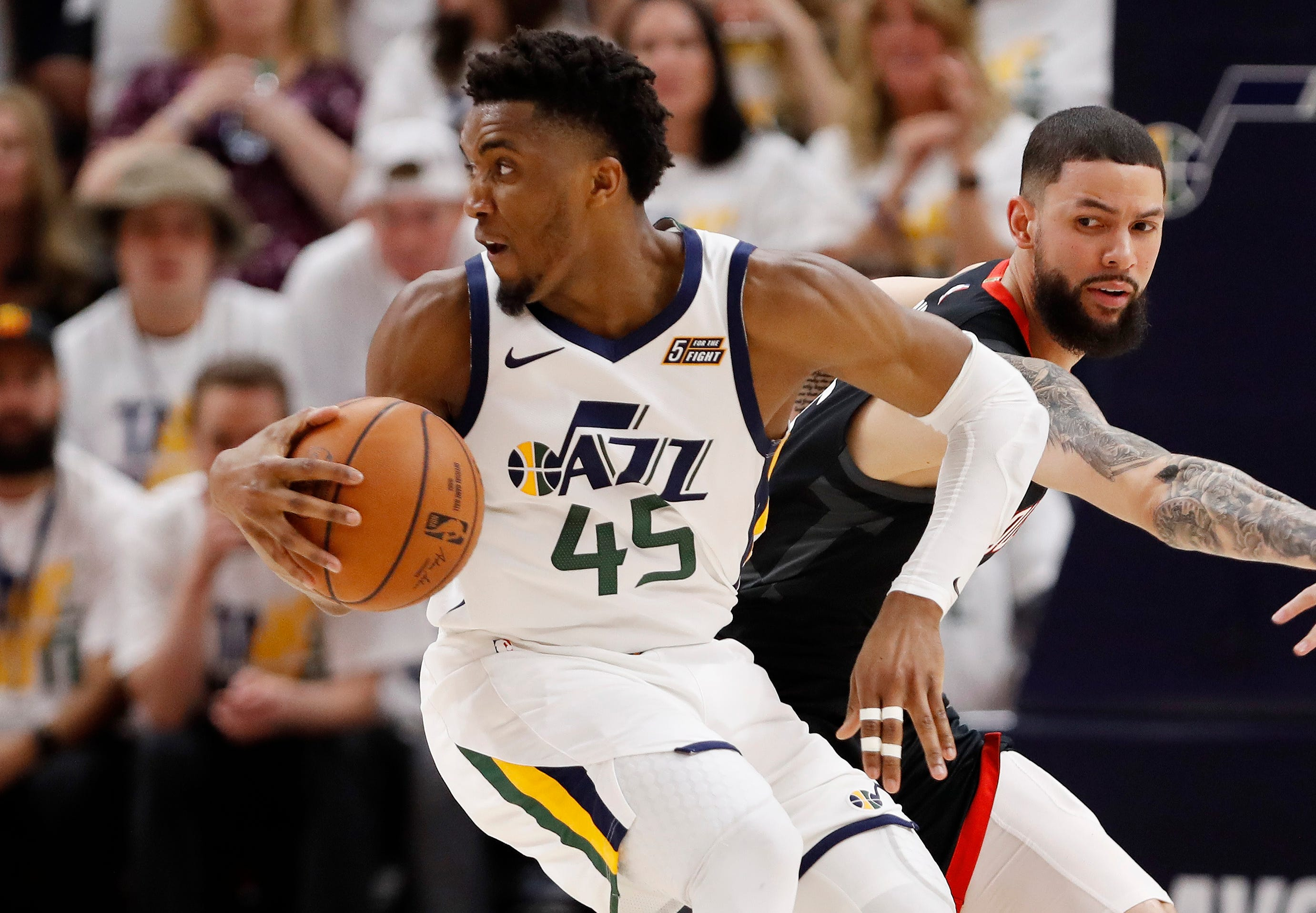 April 22: Jazz guard Donovan Mitchell (45) spins past Rockets defender Austin Rivers (25) during Game 4 in Salt Lake City.