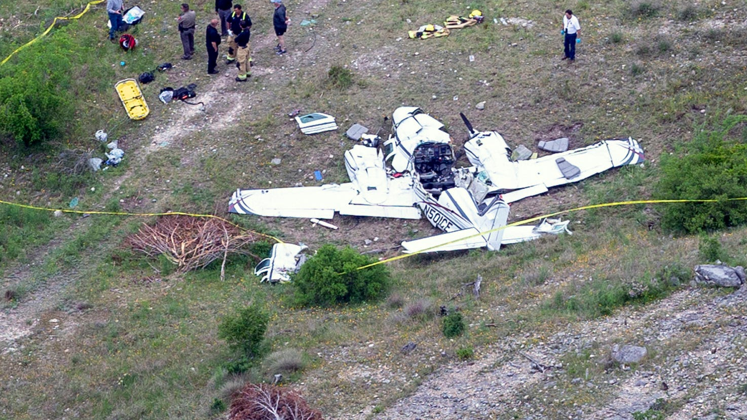 Authorities investigate at the crash scene of a twin-engine Beechcraft BE58, Monday, April 22, 2019, near Kerrville, Texas. The pilot and the five other people aboard the plane were all killed, said Sgt. Orlando Moreno, a spokesman for the Texas Department of Public Safety. (William Luther/The San Antonio Express-News via AP) ORG XMIT: TXSAE101