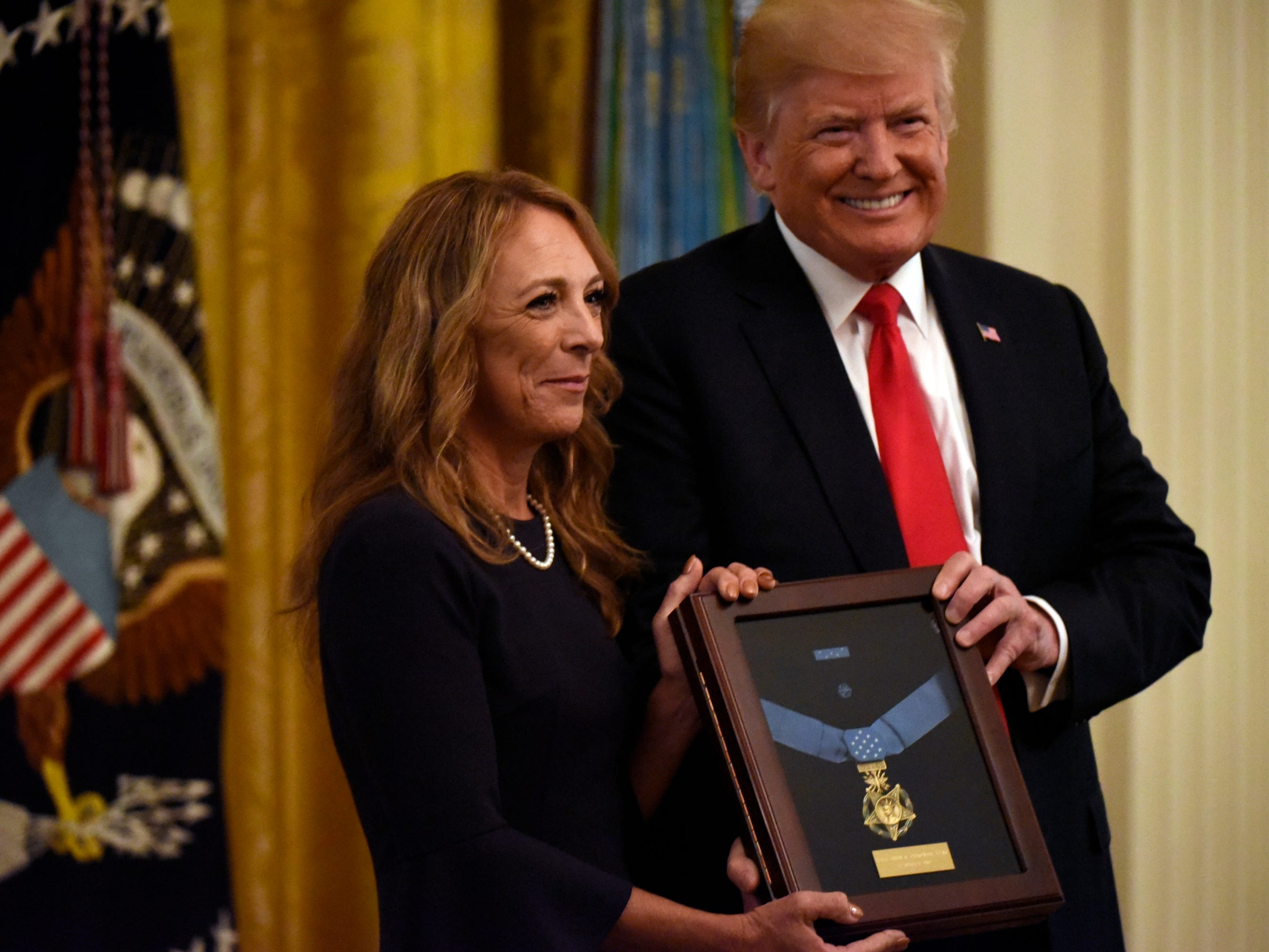President Donald J. Trump awards Sergeant John A. Chapman the posthumous Medal of Honor on August 22, 2018 in the East Room at the White House for his actions on March 4, 2002, on Takur Ghar mountain in Afghanistan. Chapman's aircraft was hit by a rocket-propelled grenade, ejecting one teammate rom the aircraft, and crippling the helicopter after it crashed in the valley below. Chapman and the remaining joint special operations team members voluntarily returned to the snow-capped mountain, into known enemy stronghold, in an attempt to rescue their stranded teammate. Sergeant Chapman's spouse, Valerie Nessel, and family joined the President at the White House to commemorate his example of selfless service and sacrifice on Aug 22, 2018.