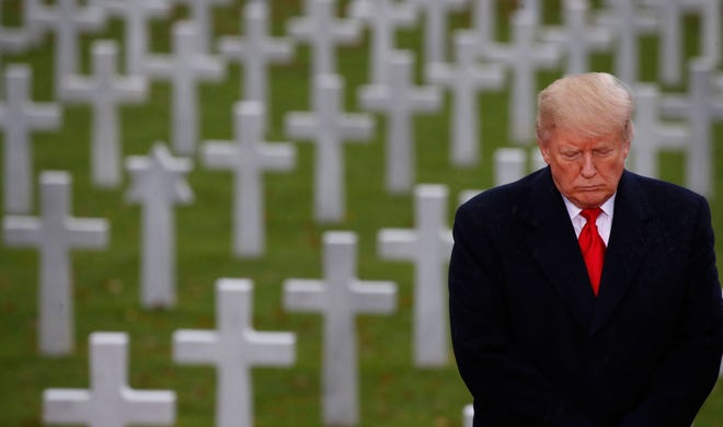 President Donald Trump stands in front of headstones at Suresnes American Cemetery near Paris on Sunday, Nov. 11, 2018.