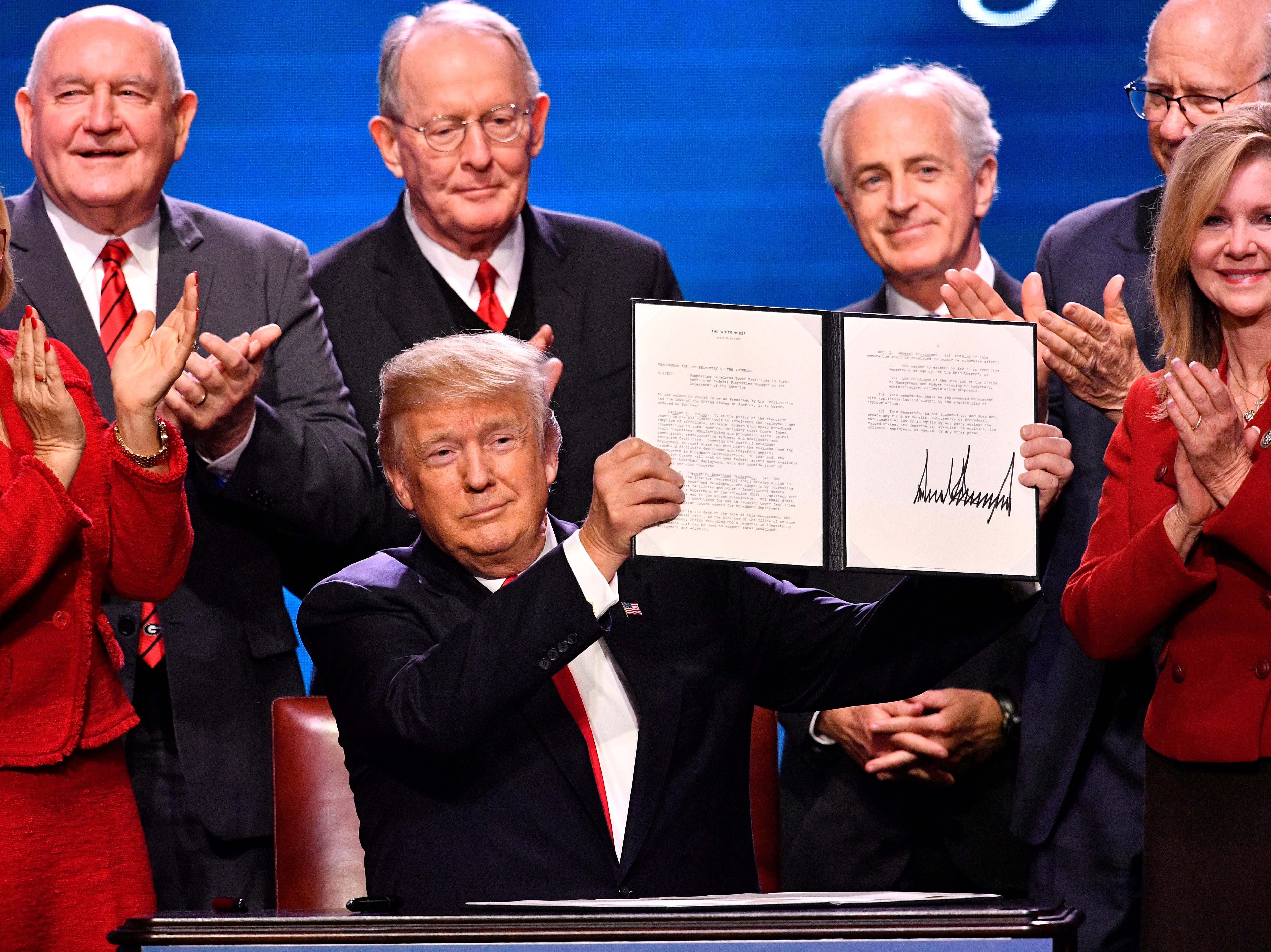 President Donald Trump holds an executive order he just signed on rural broadband flanked by Rep Diane Black, Agriculture Secretary Sonny Perdue Sen. Lamar Alexander, Sen. Bob Corker, Sen. Pat Roberts and Rep. Marsha Blackburn at Gaylord Opryland Resort & Convention Center Monday, Jan. 8, 2018 in Nashville, Tenn.