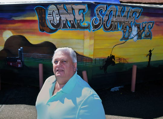 Brian Berube, co-owner of the Lonesome Dove, stands in front of a mural outside his bar in Mandan, N.D.