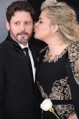 Kelly Clarkson kisses her husband, Brandon Blackstock, at the 2019 Grammy Awards.