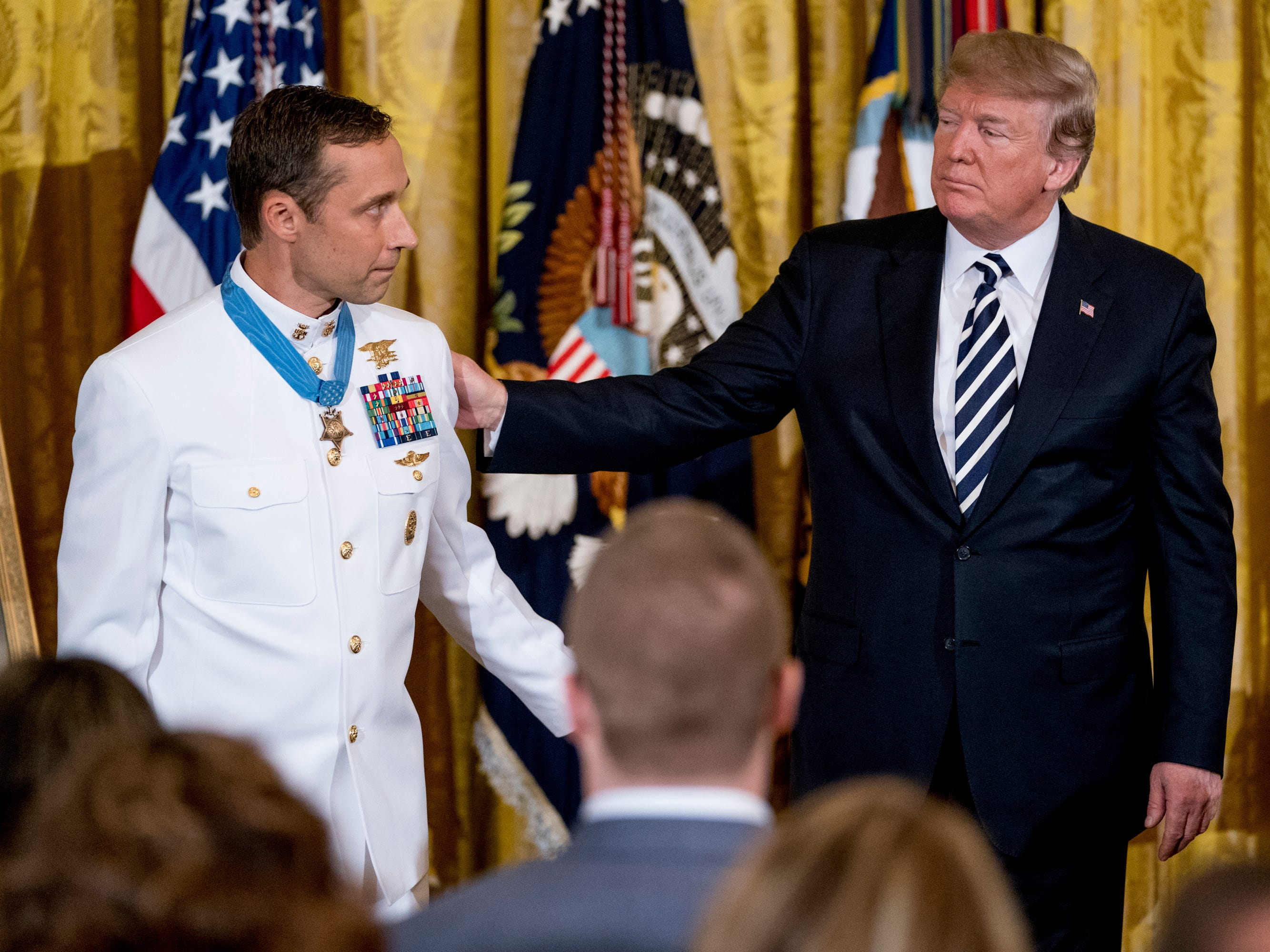 "President Donald Trump speaks with Master Chief Special Warfare Operator Britt K. Slabinski, left, after awarding him the Medal of Honor during a ceremony in the East Room of the White House in Washington, Thursday, May 24, 2018. Slabinski oversaw a daring 2002 assault and rescue mission on a snowy Afghanistan mountaintop and carried a ""seriously wounded teammate down a sheer cliff face"" while leading ""an arduous trek across one kilometer of precipitous terrain, through waist-deep snow while continuing to call fire on the enemy."""