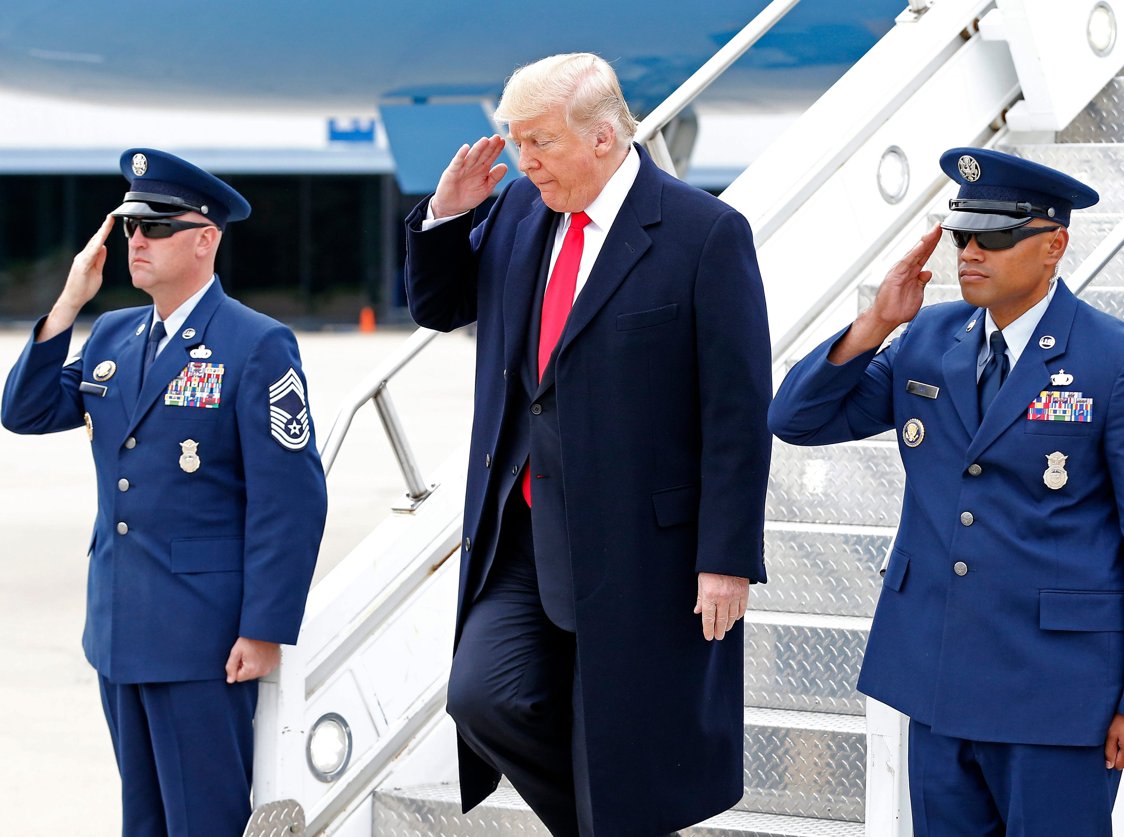 President Donald Trump salutes as he exits Air Force One after landing at Lunken Airport in Cincinnati on Friday, Oct. 12, 2018.