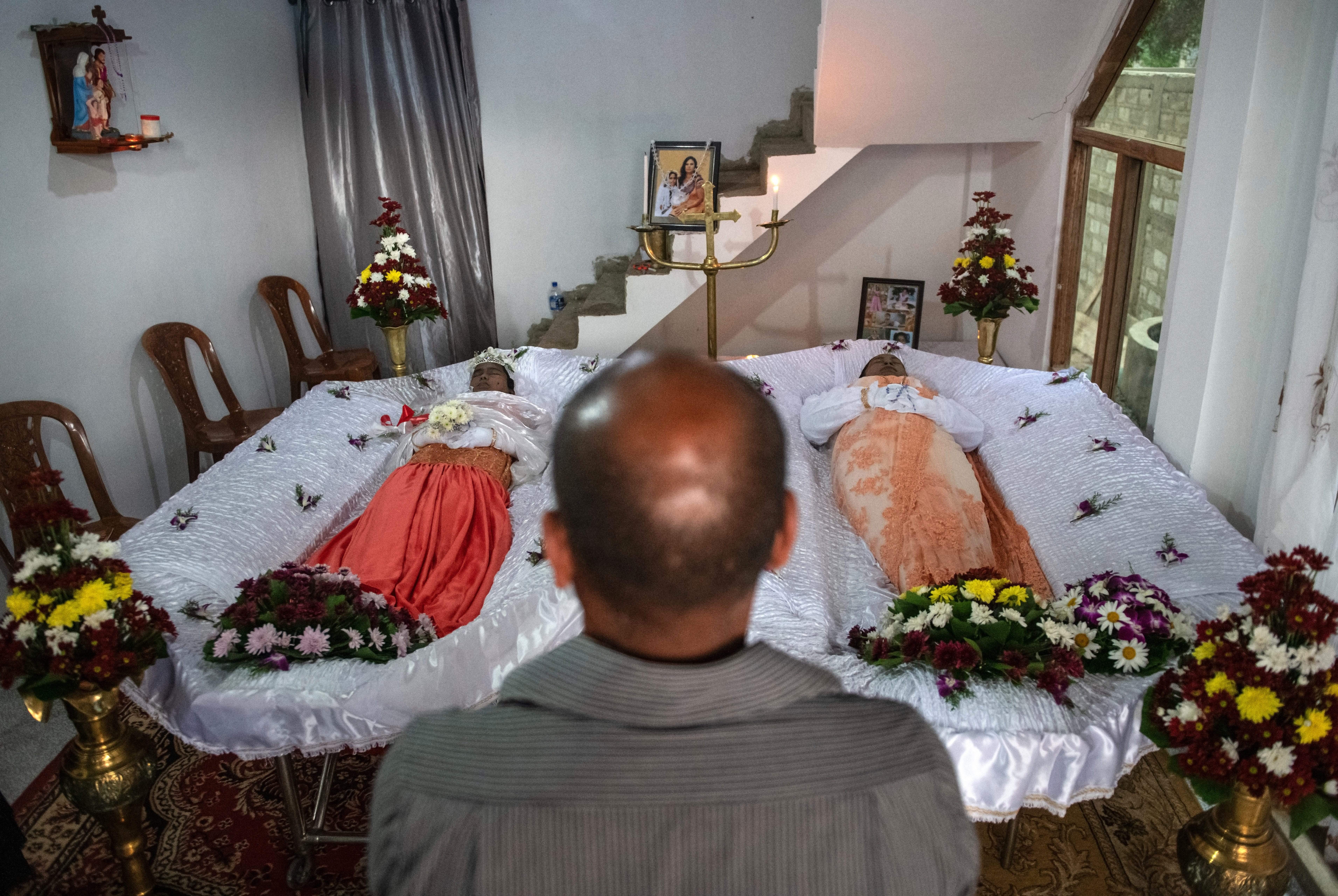 A family member looks at the bodies of 12-year-old Jiyasha Sheshani Janz, left, and her mother Dineesha Geethani de Vaas as they lie in their house during a wake after they were killed by a suicide bomber on Easter Sunday in Sri Lanka. Carl Court/Getty Images