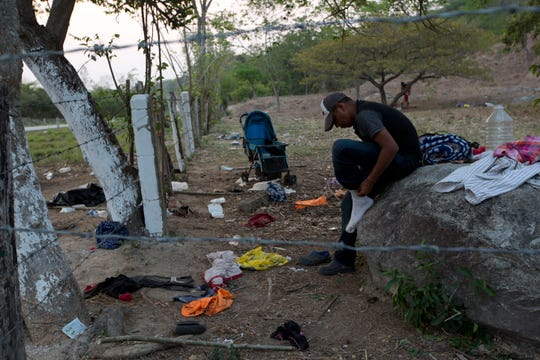 A migrant puts on the socks he'd left behind when his group evaded Mexican immigration agents by running away from the highway and into the brush in Pijijiapan, Chiapas state, Mexico, Monday, April 22, 2019. Mexican police and immigration agents detained hundreds of migrants Monday in the largest single raid on a migrant caravan since the groups started moving through Mexico last year.