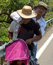 A Central American migrant pushing a child in a baby carriage is detained by a Mexican immigration agent on the highway to Pijijiapan, Mexico, Monday, April 22, 2019. Mexican police and immigration agents detained hundreds of Central American migrants Monday in the largest single raid on a migrant caravan since the groups started moving through Mexico last year.