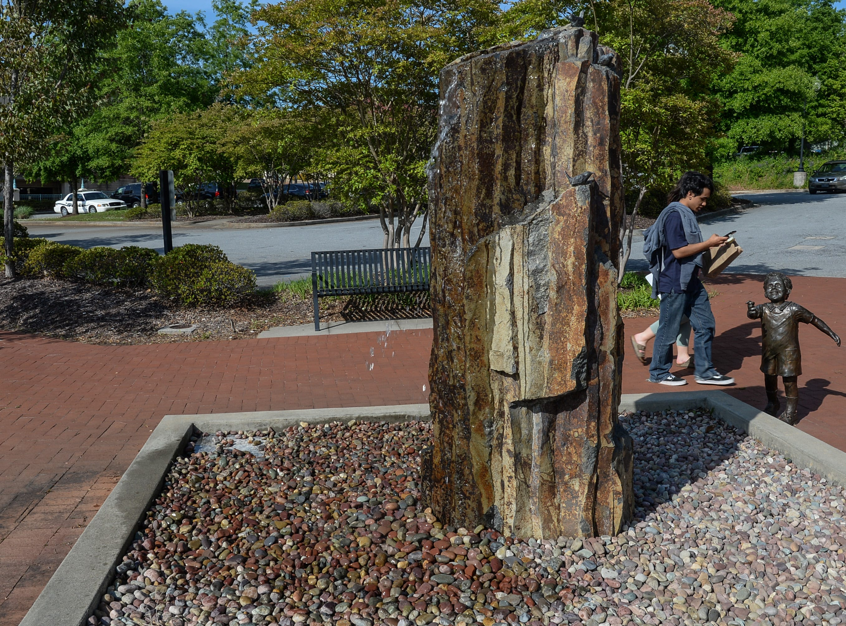 People walk by the Wren Fountain on South Main Street, a project that To Benefit Anderson group has completed since the first in 2007. The Foothills Community Foundation joined with the group in raising money for the projects.