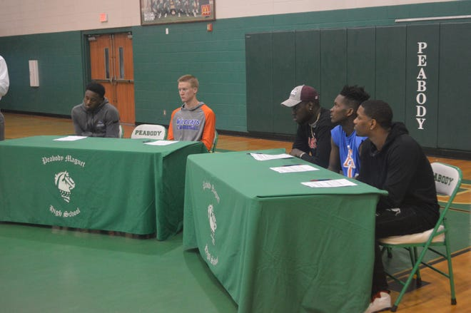 Peabody basketball players Kevin Norman (left), Caleb Howe, Jamal Hayward, Darius Smith and Kyron Gibson sign to schools Tuesday.