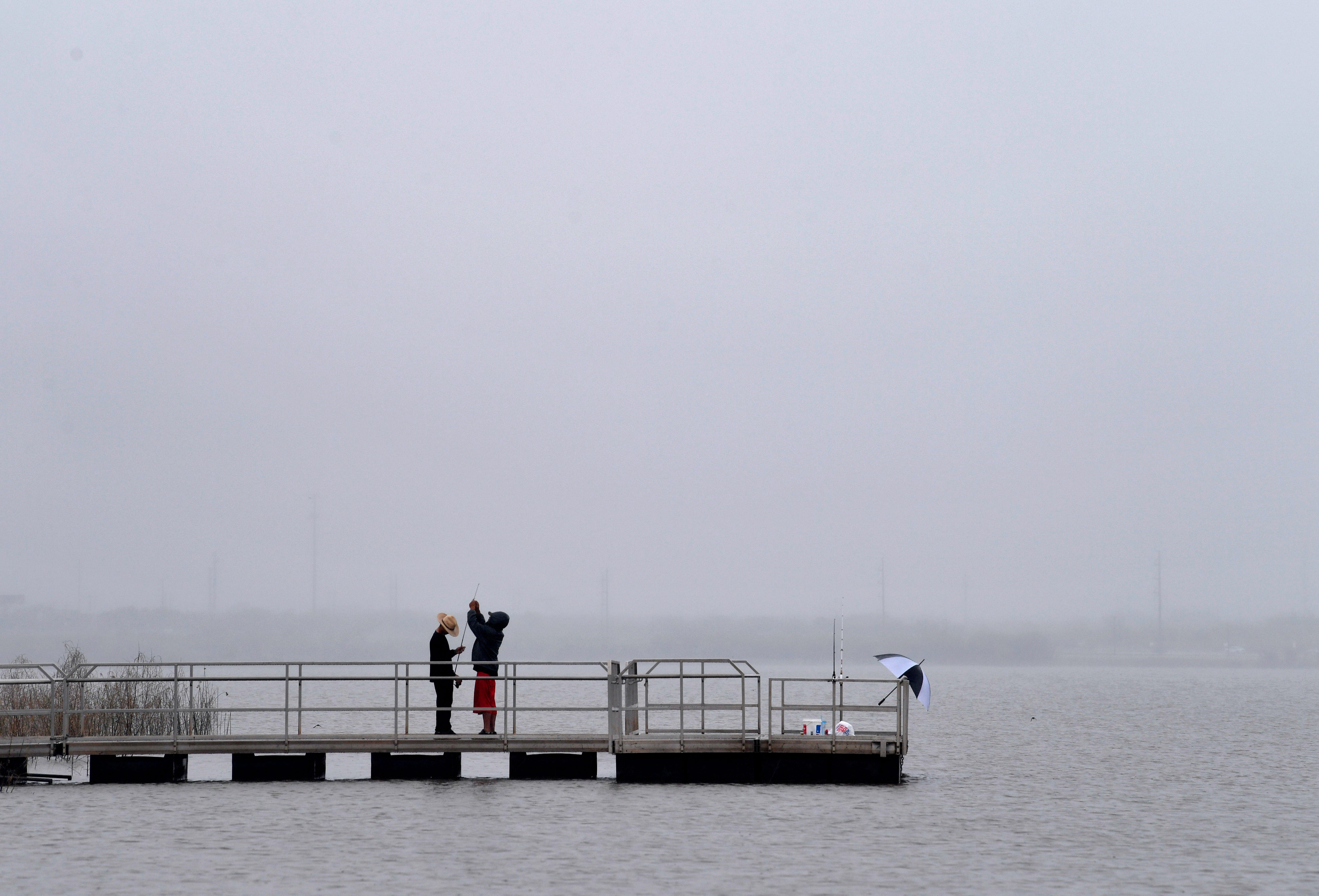 Nicholas Ontiveros (left) looks down at his reel while his father Alfonso Salazar fixes the fishing pole Wednesday April 24 at Kirby Lake. They said the fishing was light during the morning drizzle, Salazar said they were only catching small fish, and the pair packed up before the heavier rain started to move in.