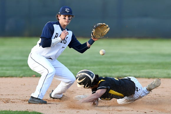 A Tuscola runner slides safely into second base just ahead of a catch by Roberson's Luke Wood during their game at Roberson High School on April 23, 2019.