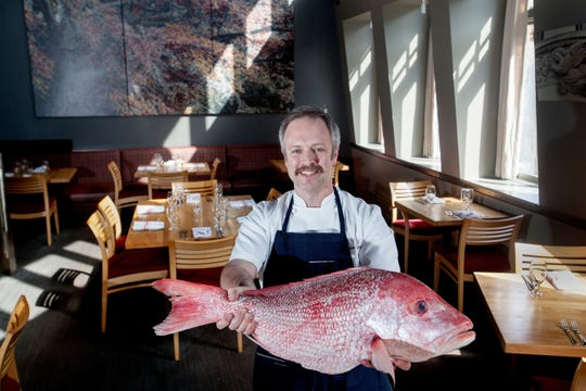 Chef William Dissen holds a red snapper at The Market Place in Asheville on Feb. 21, 2018.