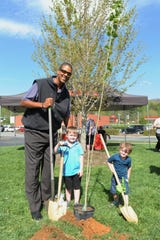 Brad Daugherty received help planting a tree outside of the Black Mountain Ingles on April 23 from Brayden and Tanner Fullbright, who were shopping in the store before the event to announce a sustainability effort between the supermarket, Kimberly-Clark Corporation and One Tree Planted.
