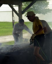 Don Wilson, front, keeps the flames under control during a Kiwinis Club chicken barbecue several years ago.
