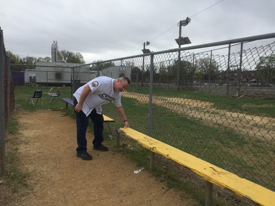 Jack O'Byrne, executive director of the Camden County Historical Society, shows the broken wood on the visitors' bench at Camden High's baseball field at Farnham Park.