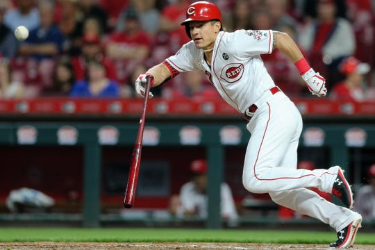 Cincinnati Reds left fielder Derek Dietrich (22) lays down a bunt in the sixth inning of an MLB baseball game against the Atlanta Braves, Tuesday, April 23, 2019, at Great American Ball Park in Cincinnati. Cincinnati won 7-6.