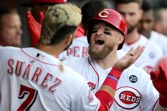 Cincinnati Reds catcher Tucker Barnhart (16), right, celebrates a home run with Cincinnati Reds third baseman Eugenio Suarez (7) in the fourth inning of an MLB baseball game against the Atlanta Braves, Tuesday, April 23, 2019, at Great American Ball Park in Cincinnati.