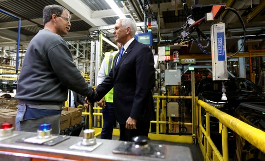 (Left to Right) Ford Motor Company Dearborn Truck Plant worker Ronny Kane, who works in the box secure station greets Vice President Mike Pence as Pence visited and toured at the plant where the Ford F150 is produced in Dearborn, Michigan on Wednesday, April 24, 2019.