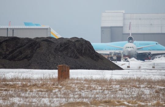 Piles of dirt dug up on the former Wurtsmith Air Force Base in Oscoda that has to remain on the property is seen by a hangar for Kalitta Air which currently operates on the location on Wednesday, March 13, 2019.