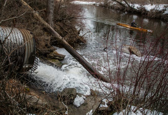 A person canoe's along Van Etten Creek in Oscoda Township on Wednesday, March 13, 2019 as a storm pipe pumps water treated at a granular activated carbon (GAC) plant from the former Wurtsmith Air Force Base into the lake leaving some PFAS foam to gather along the water.