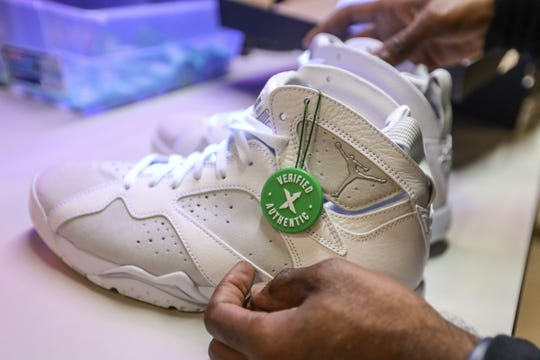 Antonio Gray, 29, of Detroit places a label on a pair of Jordan 7 retro sneakers after inspecting them the Stock X authentication center in Detroit on Tuesday, July 3, 2018.