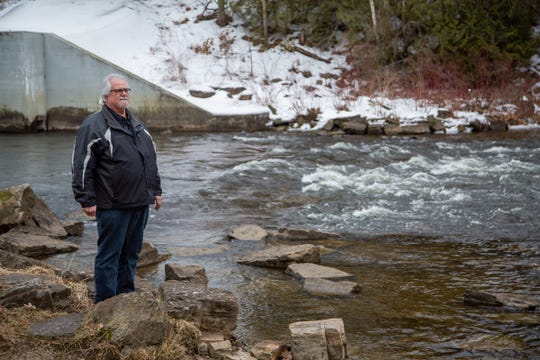 Robert A. Tasior stands next to water from the Van Etten Creek in Oscoda on Wednesday, March 13, 2019 near the dam that feeds to Van Etten Lake.