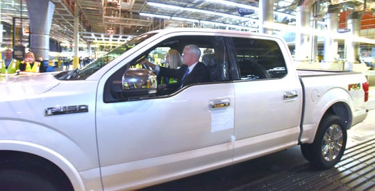 Vice President Mike Pence drives this Ford F-150 off the auto line as plant manager Debbie Manzano rides in the passenger's seat.