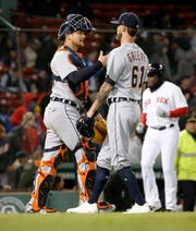 Detroit Tigers catcher John Hicks  celebrates the team's win with pitcher Shane Greene after closing out the ninth inning of the second game Tuesday.