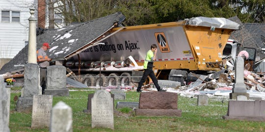 Emergency personnel secure the scene after an Ajax asphalt tractor trailer truck  slammed into a residence on 26 Mile Road just west of Omo Road in Macomb Twp., Wednesday evening.  After traveling through the residence, the truck came to rest in  Meade Cemetery.