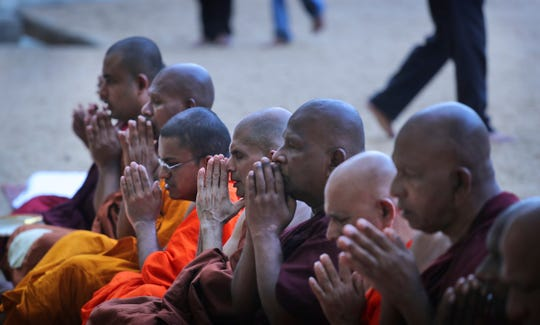 Buddhist monks pray during a ceremony to invoke blessings on the dead and wounded from Sunday's bombings at the Kelaniya temple in Colombo, Sri Lanka, Wednesday, April 24, 2019.